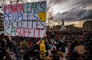 """PAR331- PARÍS (FRANCIA), 4/04/2016.- Un hombre sostiene un cartel en el que se lee """"#Papeles de Panamá, gente, crimen organizado, es suficiente"""", en un plantón del movimiento """"La Nuit Debout"""" (La Noche Arriba), en su cuarta noche consecutiva en París, Francia, hoy lunes 4 de abril de 2016. Estudiantes franceses y sindicatos se toman las calles durante este mes para protestar contra la propuesta de reforma laboral, dirigida por la ministro francés del Trabajo, Myriam El Khomri. EFE/IAN LANGSDON"""